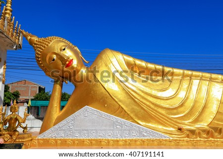 Reclining Buddha on blue sky - stock photo