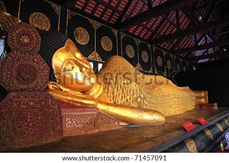 Reclining Buddha statue decorated with gold - stock photo