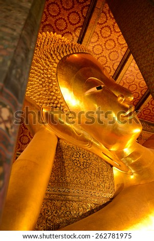 "Reclining Buddha ""Wat Pho"" is a Buddhist temple in Phra Nakhon district, Bangkok, Thailand. It is located in the Rattanakosin district directly adjacent to the Grand Palace. - stock photo"