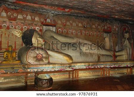 Reclining golden Buddha in the painted Dambulla Rock cave in Sri Lanka - stock photo