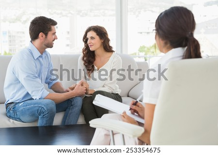 Reconciled couple smiling at each other in the therapist office - stock photo
