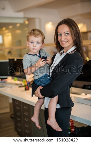 Reconciliation of family and work life: Attractive brunette woman in business attire proudly carrying a small barefoot boy in her arm in office environment - stock photo