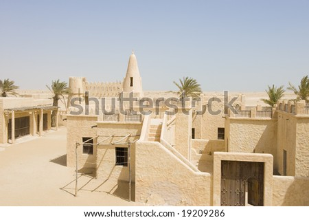 Reconstruction of a historical Arabic town in the desert. The old mosque minaret is visible in the distance. - stock photo