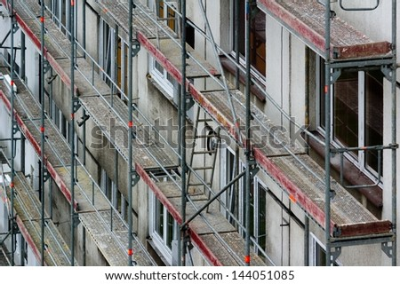 Reconstruction of block of houses with scaffolding - stock photo