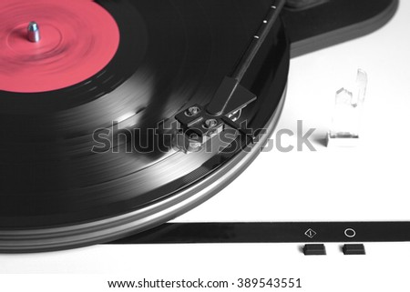 Record player in silver case with black tonearm playing a vinyl record with red label. Horizontal photo top view closeup - stock photo