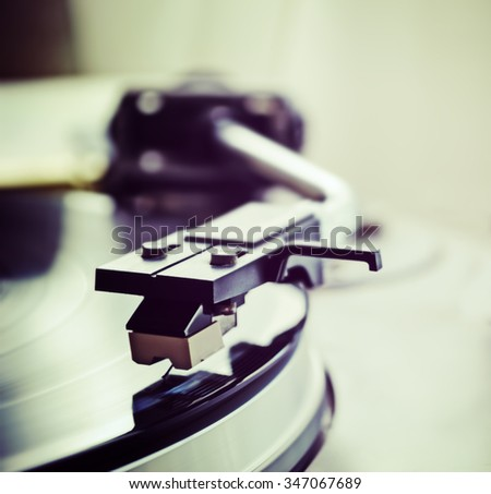 record player stylus on a rotating disc - stock photo