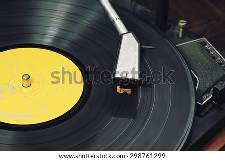 Record player stylus on a rotating disc, Picture of a vinyl record playing. - stock photo