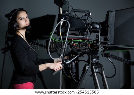 Recording at TV studio.Professional camera operator with headphones and camera in television news broadcast.Camerawoman working with big broadcasting camera.Positioned video camera.Behind the scenes - stock photo