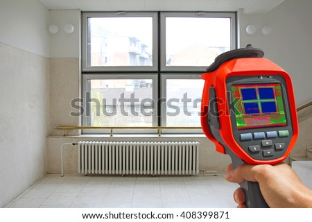 Recording Radiator Heater and a window on a building using Infrared Thermal Camera - stock photo