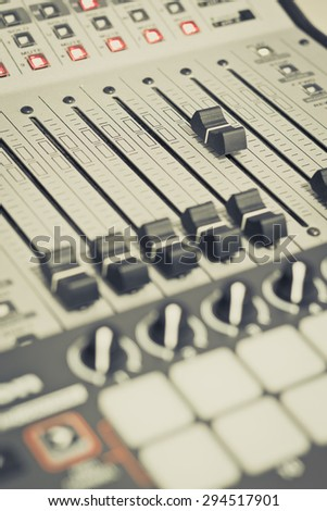 recording studio gears, broadcasting tools, mixer, synthesizer. focus on fader. shallow dept of field for music background