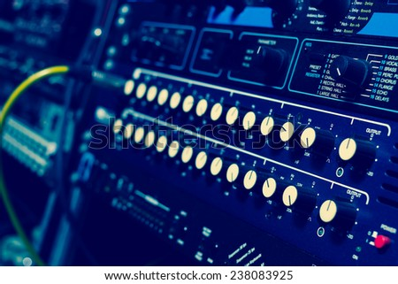 recording studio gears in rack, focus to knob & shallow dept of field / cross processed - stock photo