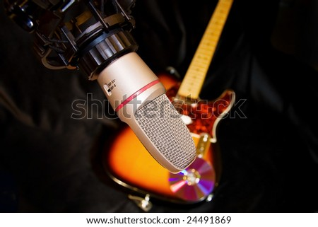 Recording studio microphone with electric guitar on black.