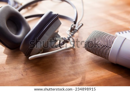 Recording vocals. An Large diaphram condenser microphone, and a professional use headphones on a rustic or bare wooden table, by the window.  - stock photo