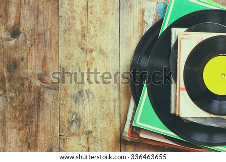 records stack with record on top over wooden table. vintage filtered  - stock photo