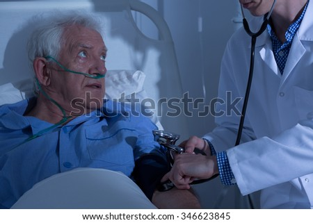 Recovering senior patient examined by doctor in hospital - stock photo