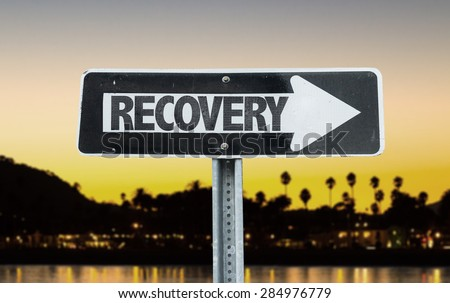 Recovery direction sign with sunset background - stock photo