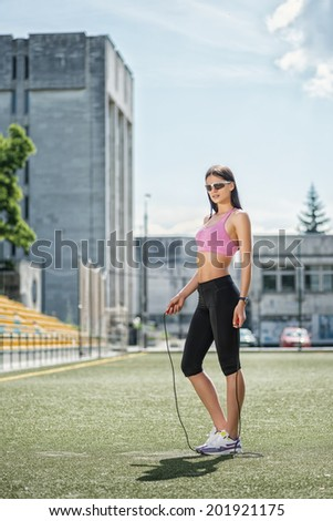 Recreation and break in training. Young and charming woman in sunglasses and sportswear standing on the football field and jumps on the rope side view - stock photo