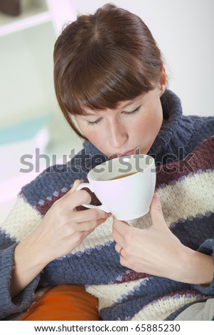 recreation at home - woman drinking tea sitting on the sofa