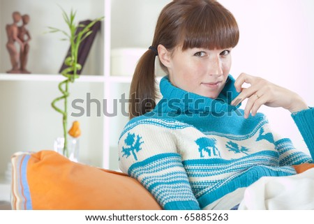 recreation at home - woman in winter clothes sitting on the sofa