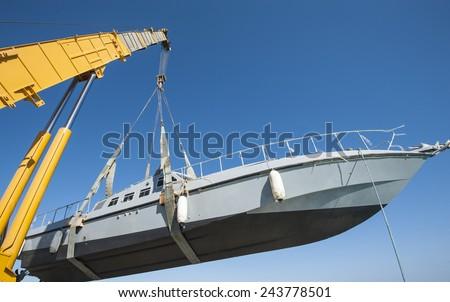 Recreational boat being lifted by heavy industrial crane machinery against blue sky background - stock photo