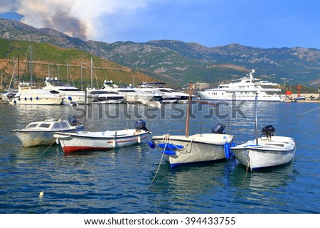 Recreational boats and distant yachts inside Adriatic sea harbor, Budva, Montenegro - stock photo