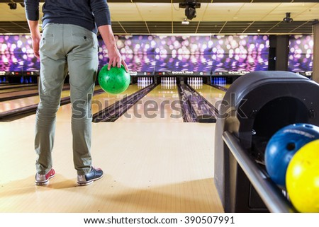 Recreational bowler with a ball in his hand waiting to take his turn and throw the ball at the 10-pins on a bowling alley - stock photo
