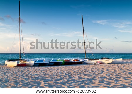 Recreational renting boats  in a tropical beach at sunset