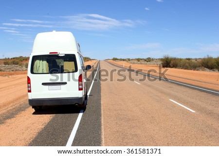 Recreational Vehicle at an endless desert highway, Australia - stock photo