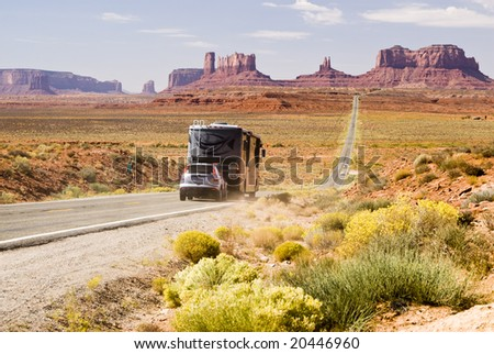 Recreational vehicle driving through Monument Valley