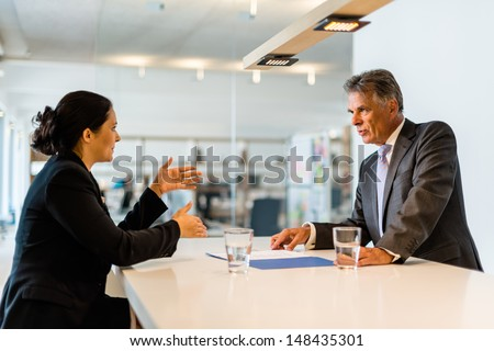 Recruiter (middle aged business man) checking the candidate, an attractive younger woman, during job interview with lively office in the background seen through glass window - stock photo