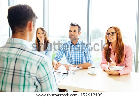Recruitment. Three corporate people Interview young man - stock photo