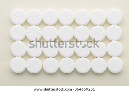 Rectangle of white pills on a light background