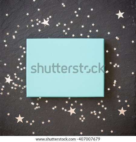 rectangular light blue box on black background with silver stars decorations. Holiday greetings. Engagement. turquoise on black board. - stock photo