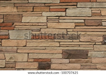 Rectangular shaped stone wall creation, in various shades of brown./ Random Horizontal Stone Wall / Great background, texture, wallpaper or as an example of past wall building ideas. - stock photo
