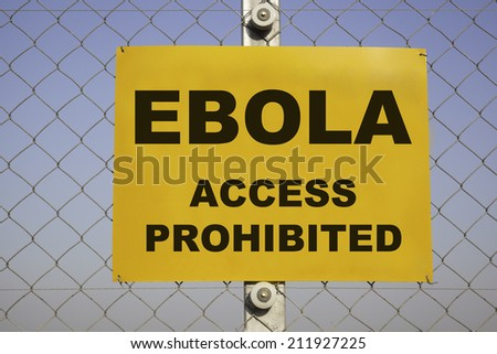 rectangular yellow danger sign at a metal chain-link fence in front of a blue sky. The caution label is warning about Ebola, Access prohibited. Concept for health risk. - stock photo