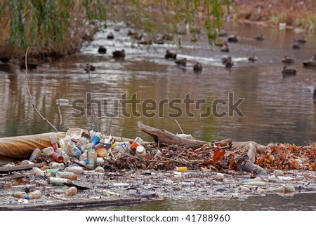 Recyclable garbage left near a duck pond - stock photo