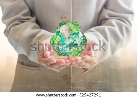 Recycle arrow sign around green globe over businessman's hands (soft focus) on blurred abstract background of city in warm tone: Eco business idea concept: Elements of this image furnished by NASA  - stock photo