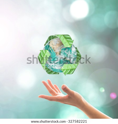 Recycle arrow sign leaf around green globe over beautiful woman human hands on blurred abstract greenery bokeh background: Recycle, reduce, reuse idea concept: Elements of this image furnished by NASA - stock photo