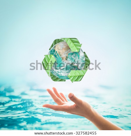 Recycle arrow sign leaf around green globe over beautiful woman human hands on blurred abstract blue water background: Recycle, reduce, reuse idea concept: Elements of this image furnished by NASA - stock photo