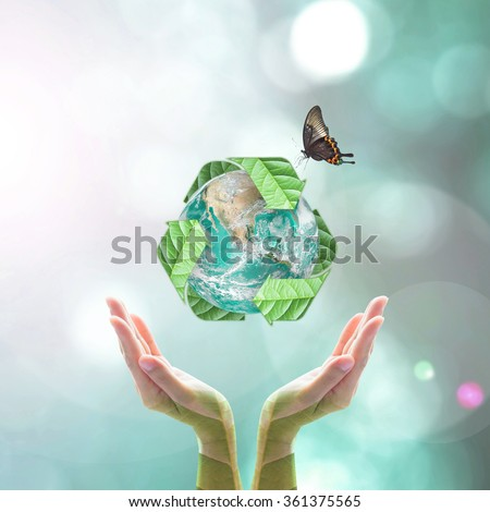 Recycle arrow sign leaf around green globe over beautiful woman human hands on blurred abstract greenery bokeh background: Recycle reduce reuse idea concept: Elements of this image furnished by NASA