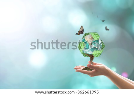 Recycle arrow sign leaf around green globe over beautiful woman human hands on blurred abstract greenery bokeh background: Recycle reduce reuse csr idea concept: Element of the image furnished by NASA - stock photo