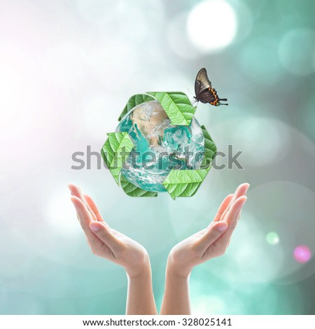 Recycle arrow sign leaf around green globe with butterfly over beautiful woman human hand on blurred abstract bokeh background: Recycle, reduce, reuse concept: Elements of this image furnished by NASA