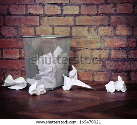 Recycle bin filled with crumpled papers. Brick wall background. Retro style - stock photo