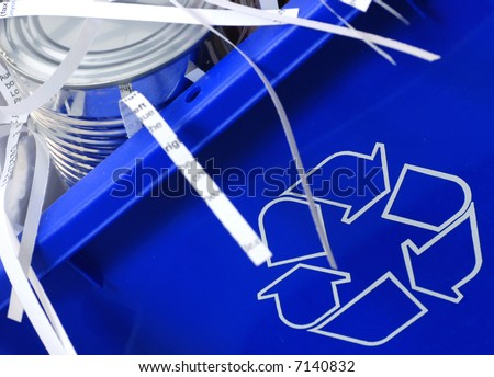 recycle bin filled with tin can and shredded paper - stock photo
