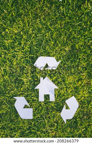 Recycle building material or build responsibly - white cutout house and a recycle sign over green grass with copy space. - stock photo