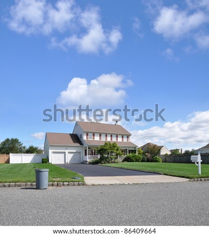 Recycle Can in Front of Residential Suburban High Ranch Home with Two Car Garage Blacktop Driveway Mailbox on Front Lawn Sunny Blue Sky with Clouds