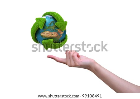 Recycle globe with green arrows covered with grass presented on female finger - stock photo