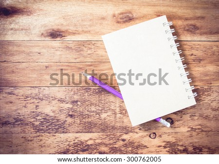 recycle notebook and wooden pencil purple on wood background - stock photo