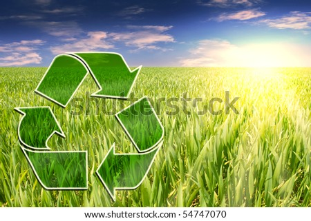 recycle sign on grass field with sunbeams and cloudy sky in back - stock photo