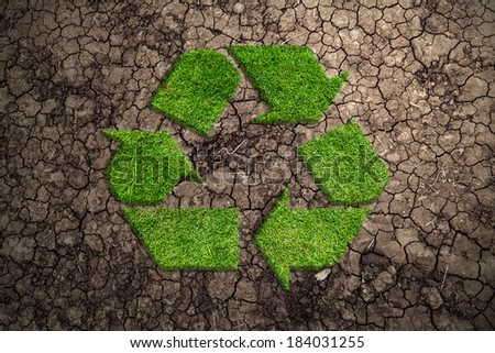 Recycle symbol in the form of a grass against the dry earth.  - stock photo